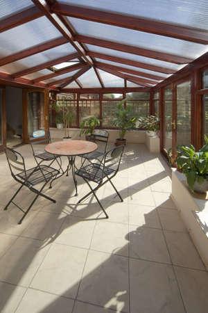 wintergarten: Wintergarten Tischen, Sesseln Pflanzen Zimmer im Haus neben dem Garten Lizenzfreie Bilder