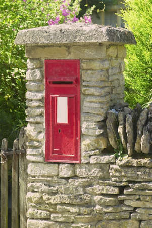 A postbox in a wall outside house in cotswold village. photo
