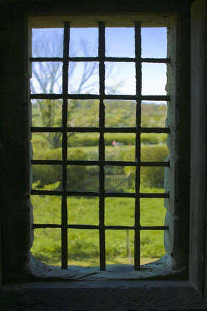 ancient prison: An old medieval window with bars in a castle looking at countryside outside.