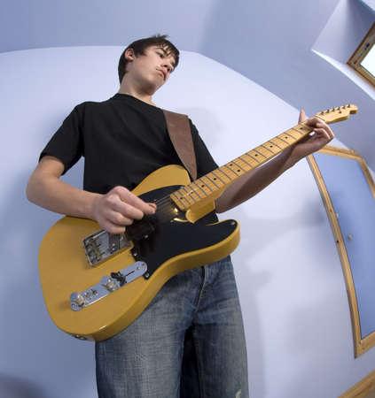teen bedroom: guitarist teenage boy playing guitar