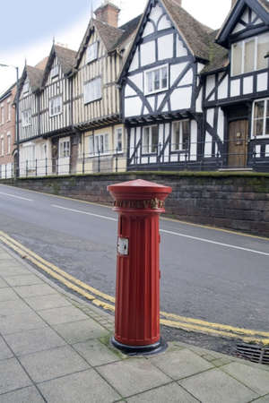 A victorian postbox and the half timbered housesin the centre of warwick. photo
