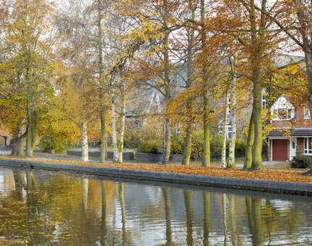 Trees in autumn leaf alongside a waterway.