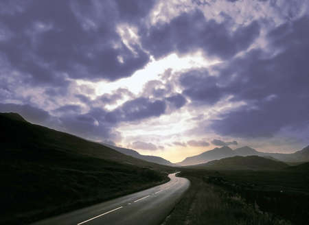 A road through mountains with a sunset sky, view of highway and hills, in an evening sunset or morning sunrise.