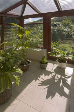 A conservatory with tables chairs plants room in house next to garden