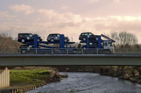 shipper: A car transporter carrying range rovers  crossing a bridge over a river