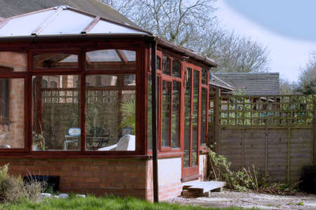 A conservatory with tables chairs plants room in house next to garden photo