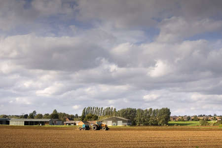 ploughing field: tractor ploughing a field of earth Stock Photo
