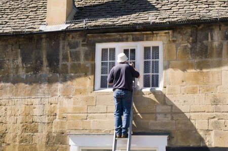 un hombre pintando una casa de una escalera Foto de archivo - 3470638