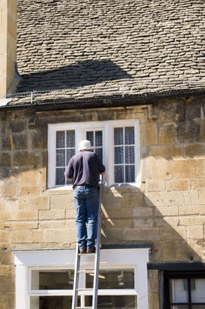 a man painting a house from up a ladder photo