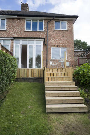 house with wooden decking and patio leading to garden photo
