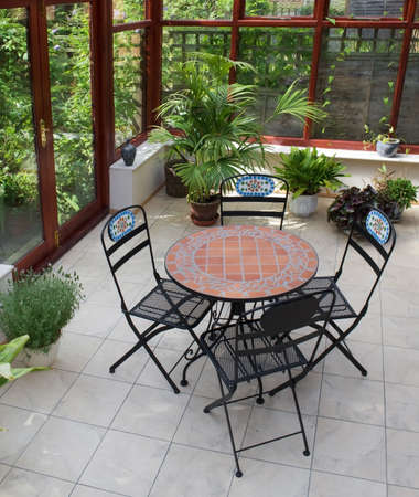 conservatory: conservatory tables chairs plants room in house next to garden