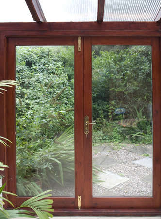 conservatory with door to garden and plants, a room in house next to garden