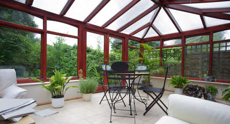 conservatory tables chairs plants room in house next to garden Stock Photo - 3567125