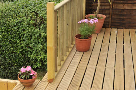 house with wooden decking and patio leading to garden Stock Photo