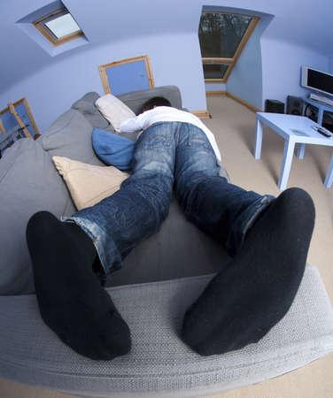 teenage boy sleeping on couch Stock Photo