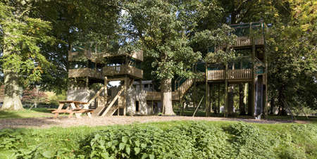 An adventure playground made from wood with walkways photo