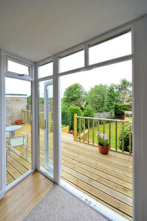 a house with wooden decking and patio leading to garden photo