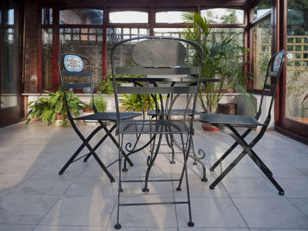conservatories: A conservatory with tables,chairs & plants in room in house next to garden.