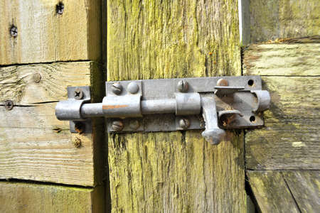 housebreaking: locks and bolts on old wooden gate made of wood Stock Photo