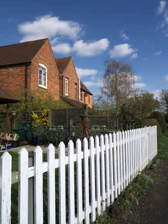 cottages in a row with a white picket fence