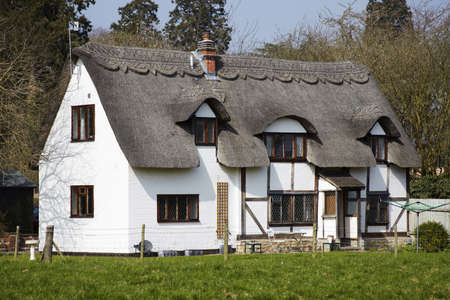thatched cottage in an english village photo