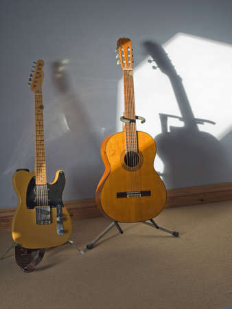 nylon string: two guitars in sunlight and shadow one an electric telecaster the other a spanish nylon string acoustic