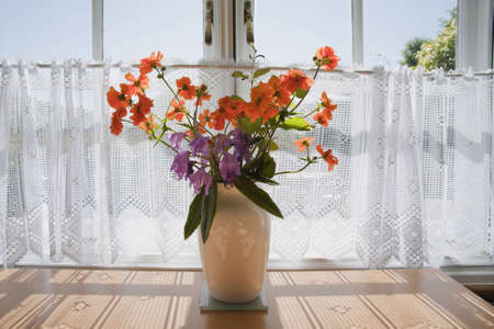 cut flowers in a vase on a table inside a cottage