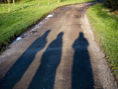 the shadows of three people walking down a road