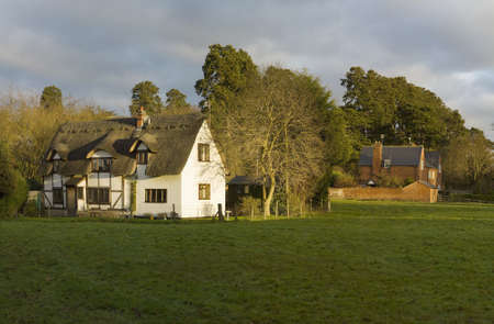 english village: farm house and cottage in a field in the countryside Stock Photo