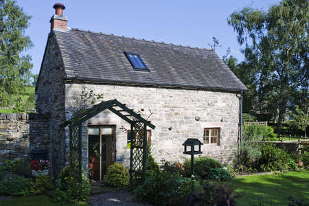 an old stone cottage with a garden in a village photo