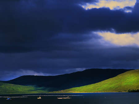 fishingboats: view across the sound of raasay from the isle of skye to the scottish mainland with fishingboats on the sea and a trout hatchery. threating clouds over the mountains.