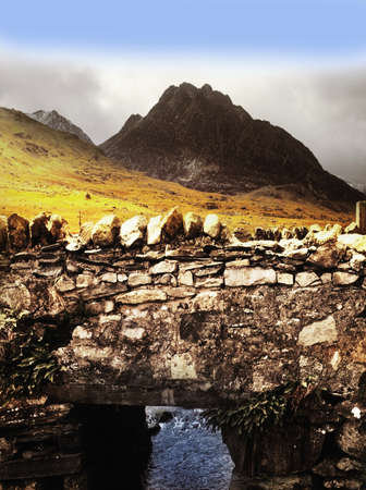 nant: tryfan mountain from old stone bridge over river ogwen, nant ffrancon pass, snowdonia national park, wales , uk, gb Stock Photo