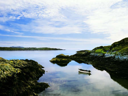 moorings: a fishing boat moored on a still sea in a cove, schull bay, mizen peninsula, countty cork, west coast of ireland, europe eu