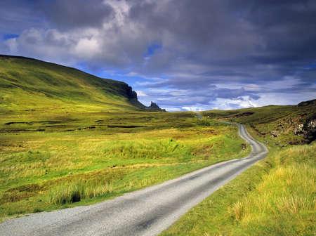 eine öde Landstraße durch Moorlandschaften auf der Isle of Syke mit dem Quiraing in der Ferne - die Isle of Skye in Schottland, Grossbritannien UK
