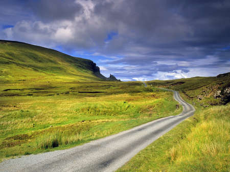 una carretera desolada entre páramos en la isla de Syke con la Quiraing en la distancia - la isla de Skye, en Escocia, Gran Bretaña, Reino Unido