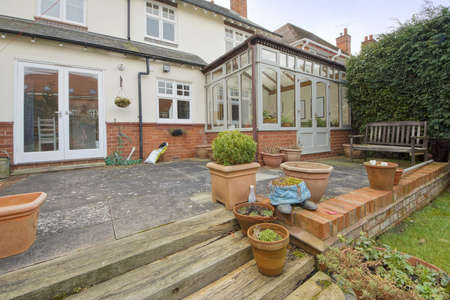 conservatory: a rear view of a house with a conservatory and garden