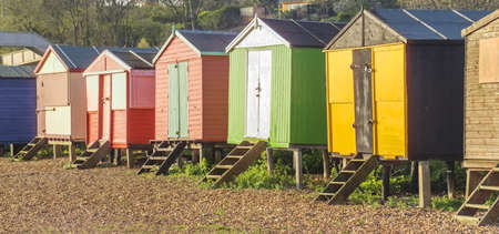 huts: a row of beach huts on a sandy beach with sand dunes behind
