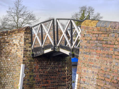inland waterways: a brick built bridge with black and white metal struts and a horse rope gap on a canal on the inland waterways network of navigable canals and waterways in the english and british countryside in the uk, united kingdom