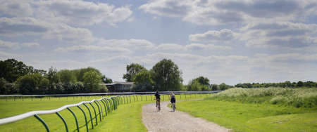 couple cycling on cycle track around warwick racecourse park, midlands, uk