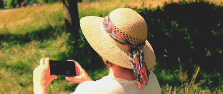 stately: Woman in straw hat visiting stately home using mobile smart phone to take photograph  Stock Photo