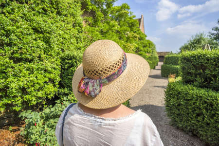 straw the hat: Woman in straw hat in garden