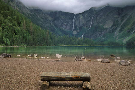 A rough hewn wood bench made of logs is sitting on the rocky shore of Avalanche Lake in the mountains of Glacier National Park, Montana. Low clouds can be seen at the top of the frame. Horizontal shot. photo