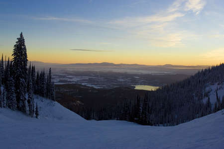 expansive: A lake and expansive valley floor are seen from the top of a snowy ski run at twilight. Horizontal shot.