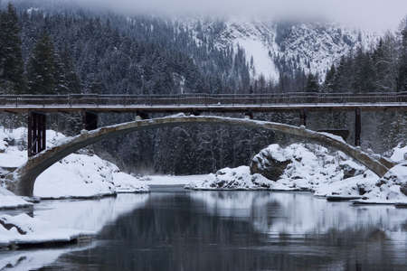 flathead: Scenic view of the original Glacier National Park entrance bridge spanning the Flathead River in a winter landscape. The water is reflecting the snow-covered riverbanks and the trees on the mountain in the background. Horizontal shot. Stock Photo