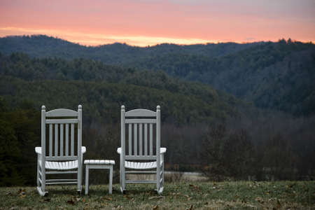 silla de madera: Par de blancos mecedoras de madera y una tabla coincidente se encuentran en un c�sped de la cima de la colina con vistas a las colinas boscosas del Parque Nacional de las grandes monta�as humeantes al atardecer. Horizontal a tiros.  Foto de archivo