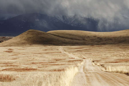 A storm cloud is passing over a barren landscape with snow-covered mountains in the background. A dirt road can be seen receding into the distance across the National Bison Refuge in Montana. Horizontal shot. photo