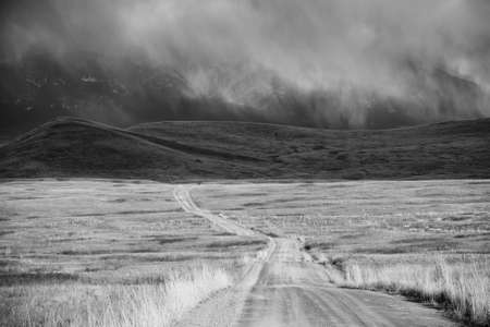 Black-and-white image of a storm cloud passing over a barren landscape with snow-covered mountains in the background. A dirt road can be seen receding across the National Bison Refuge into the distance of Montana. Horizontal shot. photo