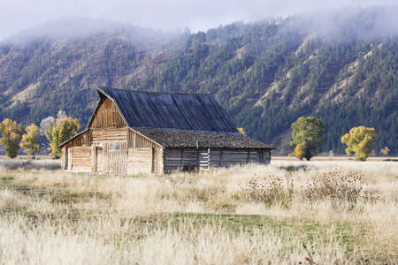 An abandoned barn is sitting in an overgrown field with a tree covered mountainside in the background. A fog is beginning to set down from the mountains. Horizontal shot. photo