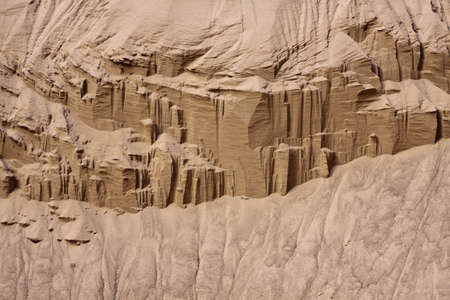 cliff face: Cliff face eroded away by wind leaving dry sand at the bottom and causing geometric patterns to form on the face. Horizontal shot.