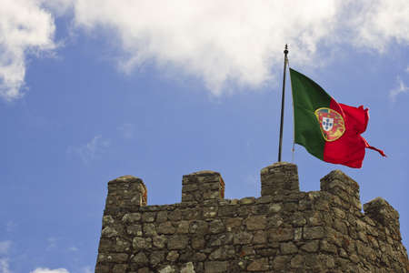 portugal flag: A flag is flying above the stone battlement of an ancient castle tower. Horizontal shot.